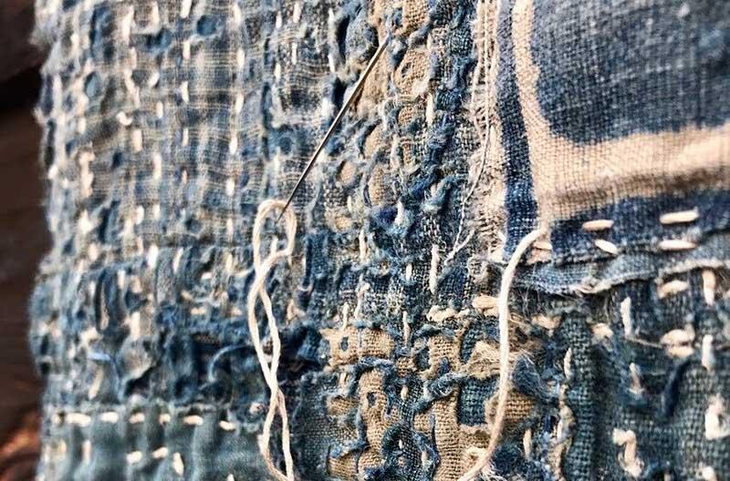 Närbild på sashikobroderi med vit tråd mot indigoblått tyg.