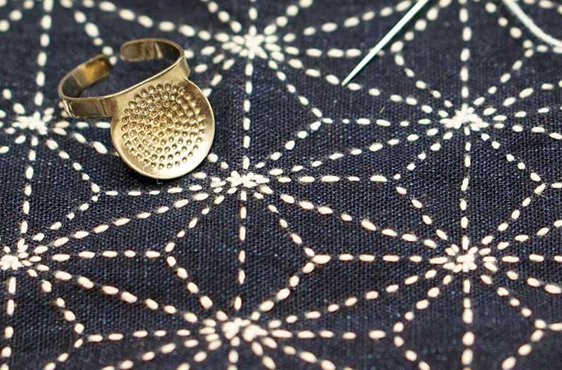 Geometriskt mönster som byggs upp av små vita stygn sydda på mörkblått tyg. Mönstret är vanligt inom sashiko.