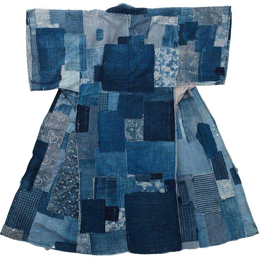 Kimono sydd av ett hundratal lappar i blå nyanser. Många av lapparna har olika mönster: ränder, rutor eller reservagetryckta botaniska motiv i vitt.