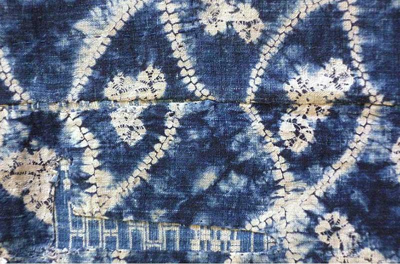 Vita mönstringar mot indigoblå botten. Mönstren består av oregelbundna former som byggs upp av prickar och batiksolar.