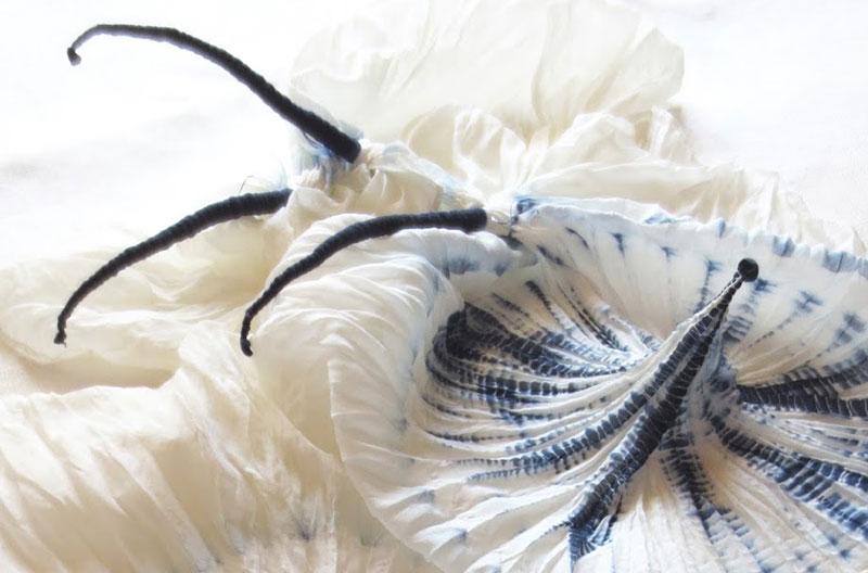 Vitt tyg som är hårt ihopknutet med blå tråd. Där tråden avlägsnats bildar tyget skulpturala toppar.