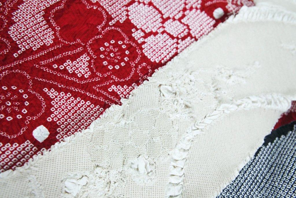 Kyo kanoko shibori. Rött, vitt och blått tyg. Det röda och blå tyget har ett småskaligt mönster av ringar i vitt. Det vita tyget visar alla knutar som skapat mönstret vid infärgningen.