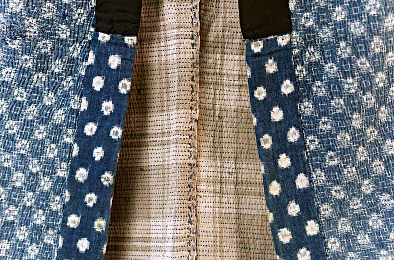 Närbild på jacka med beige foder och utsida av blått tyg med mönster av vita snöbollar.