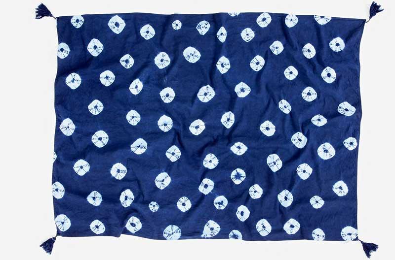 Maki age shibori. Indigoblå scarf med mönster av vita ringar med blå mitt. Ringarna har oregelbunden form.