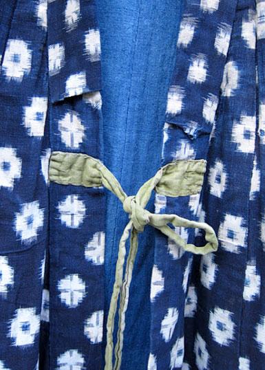 Utsnitt av ett kasurimönstrat klädesplagg i bomullsväv. Mönstret har blå botten och vita snöblollar, cirka 2 cm i diameter.