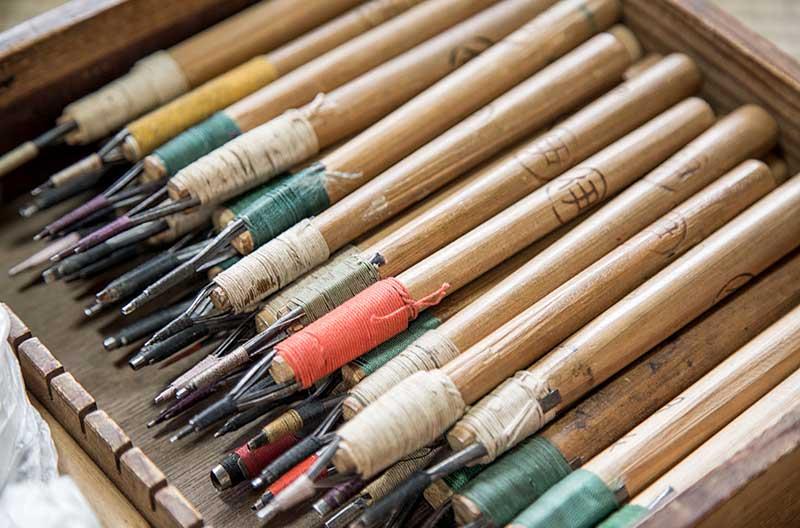 Verktyg med vassa spetsar av metall. Spetsarna är fastsurrade med tunn tråd på skaft av bambu.