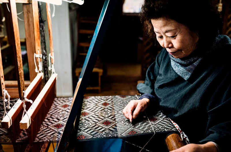 Äldre, japansk kvinna vid vävstol. Väven har ett mycket komplext mönster av svarta och roströda trådar.