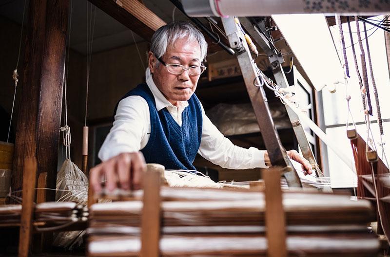 Äldre, japansk man arbetar vid vävstol.