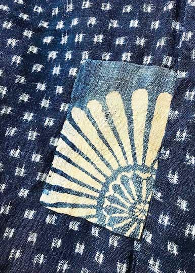 Blå indigoväv med mönster av vita prickar (kasuri). Ovanpå det är en lapp fastsydd med en stor vit blomma mot ljusblå denim.