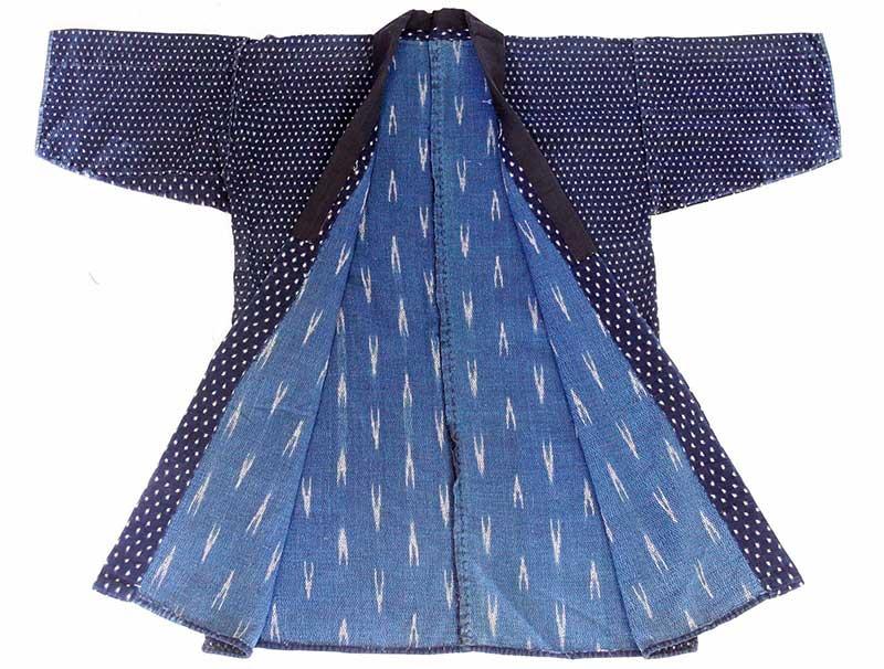 Äldre jacka med mörkblå utsida med vita små prickar, och mellanblå insida med vita pilspetsar.