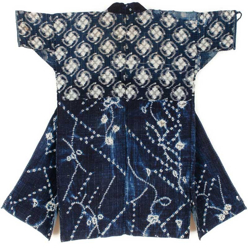 Ett kimonoliknande plagg sett bakifrån. Plagget består av två olika vita mönster mot blå botten: ett slags snurror, ca 8 cm stora, och ett oregelbundet mönster av prickar och små solar.