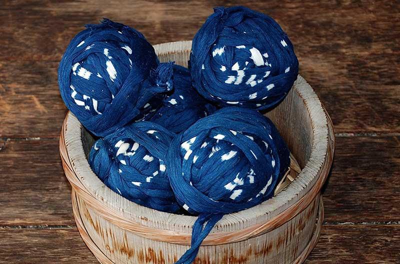 Flera nystan med garn infärgat med ikat. Garnet har blå och vita partier. Blått dominerar.