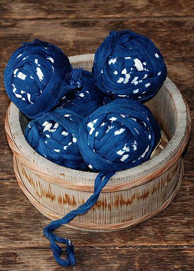 Flera nystan med kasurimönstrat garn i blått och vitt.