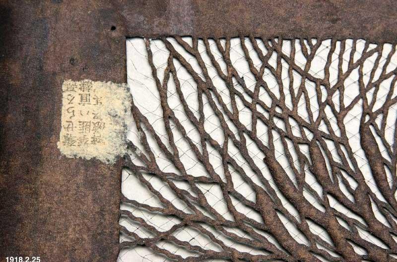 Närbild på en mycket gammal tryckschablon. Mönstrret är fint utskuret och de smala mönsterdelarna hålls ihop av tunna trådar av silke.