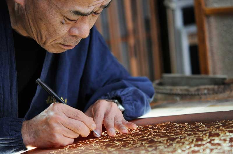 En äldre japansk man skär ut ett mönster ur en tryckschablon som används vid katazome.