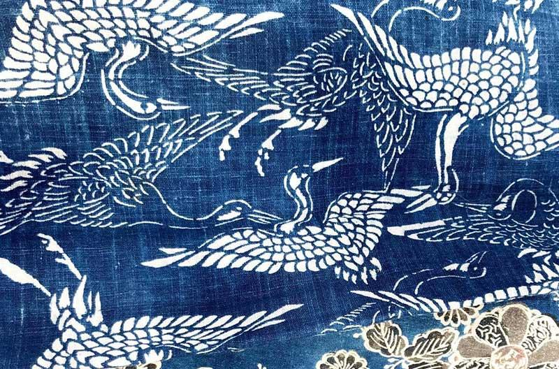 Blått denimtyg med ett mönster med vita, stiliserade tranor.