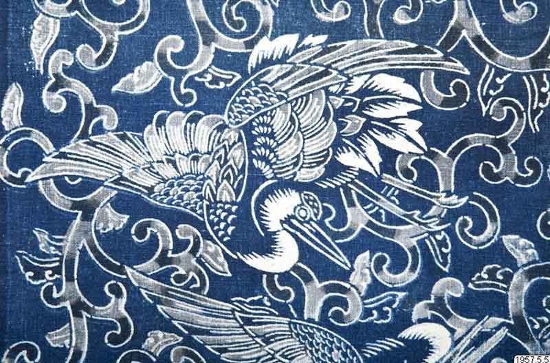Blått tyg med en stor vit trana omgiven av sirliga ornament. Mönstret är tryckt med katazome.