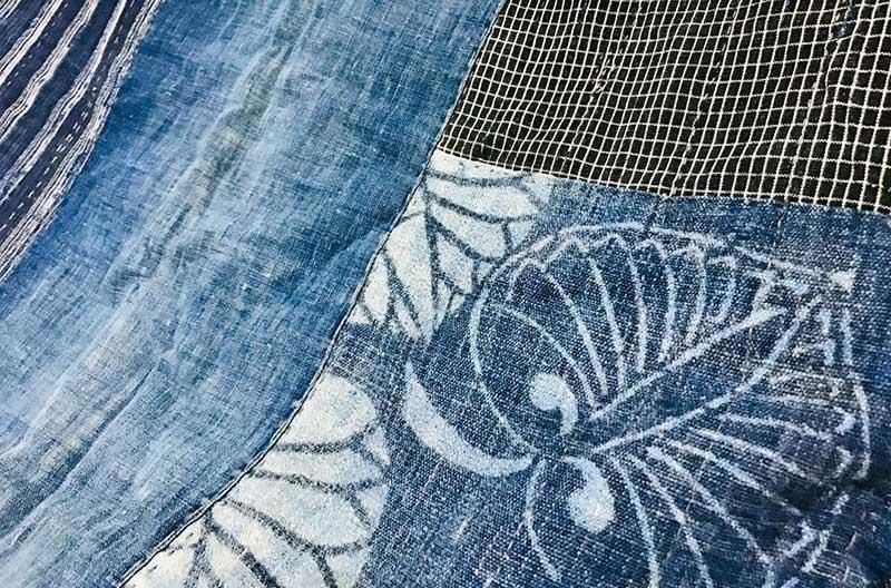 Tyglappar i ljusblå denim och rutig bomullsväv. En av lapparna har ett vitt mönster med stiliserade blad.