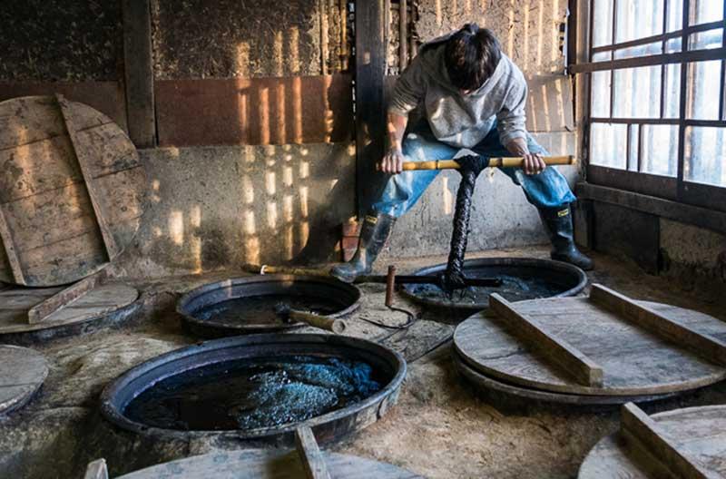 En man står böjd över ett hål i marken där en stor garnhärva just färgats in. Mannen vrider garnhärvan med hjälp av en pinne.