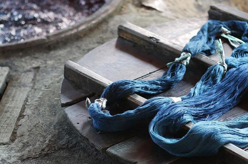 Två stora garnhärvor med blått garn. Garnet är ombundet med vita band på flera ställen.