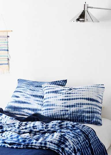 Utsnitt från ett sovrum med kuddar och sängkläder i indigoblått och vitt med organiska shiborimönster.