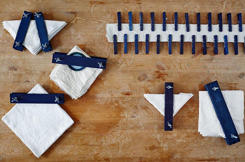 Ita-jime shibori. Sex exempel på hur ett tyg kan vikas och pressas ihop i sin vikta form med hjälp av klädnypor och träblock. Tyget är vitt och ännu ofärgat.