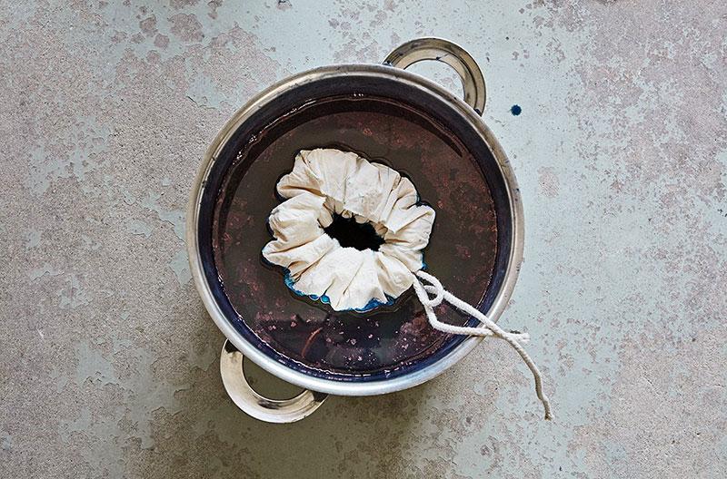 Ett vitt tyg har dragits ihop till en ring med hjälp av snören. Tyget ligger i ett färgbad med indigo i en stor kastrull.