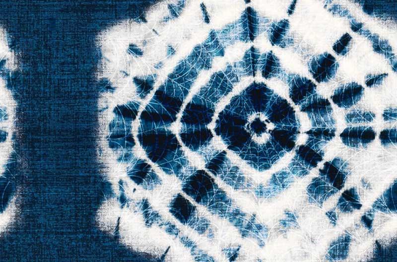 En stor vit mönsterbild mot indigoblå botten. Mönsterbilden liknar en strålande sol eller blomma och påminner om knytbatik.