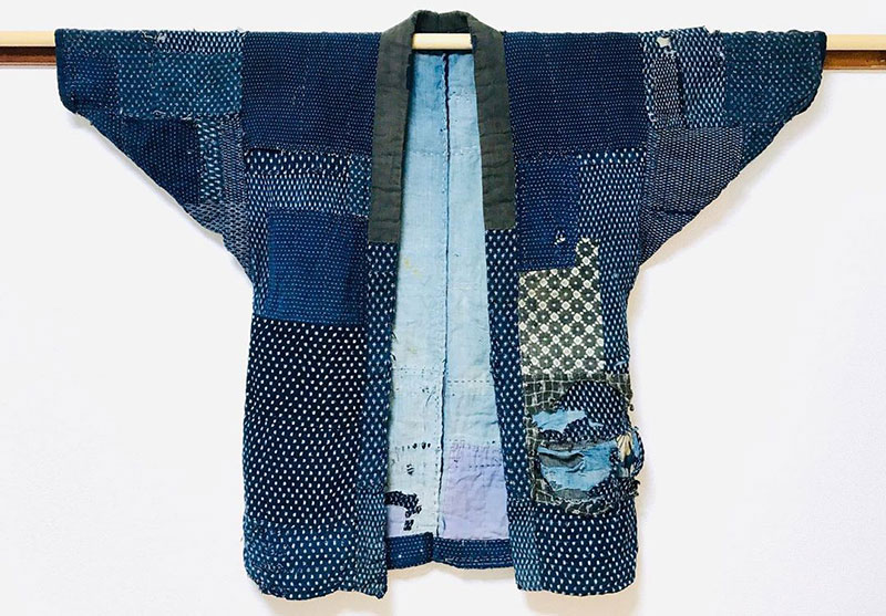 En sliten jacka som består av ett trettiotal indigoblå lappar med vita prickar. Några lappar har avvikande mönster.