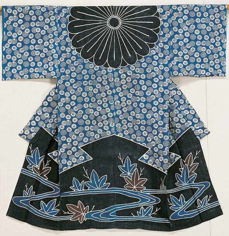 Kimono i blått, vitt och svart. Stora delar av kimonon har ett mönster med blommor, ca 5 cm i diameter. Nedre delen har ett mönster med stora lönnlöv och rinnande vatten.