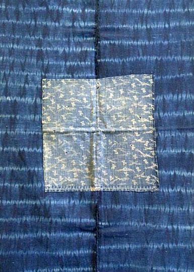 Indigofärgad bomullsväv med ett randmönster i ljusare blått. Ränderna har mjuka färgövergångar. Ovanpå en lapp med ett nätt, vitt bladmönster mot blå botten.