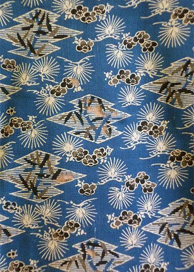 Mönster med blommor och solar i vitt och brunt mot blå botten. Tyget är ett glänsande sidentyg.
