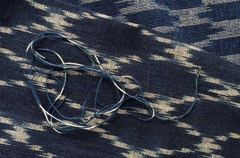 Naturfärgat mönster mot djupblå botten. Mönstret har diffusa konturer och föreställer diagonala rutor. Ovanpå tyget ligger en garnslinga i med blå och naturfärgade partier.