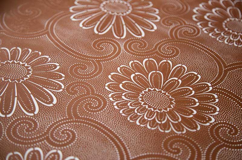 Närbild på pappersschablon med mönster av stiliserade krysantemer. Kring blommorna finns ett mönster av ornament och mycket små prickar.