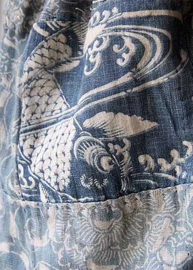Lappar i blå och vita nyanser med motivet av en stor karpfisk i vitt.