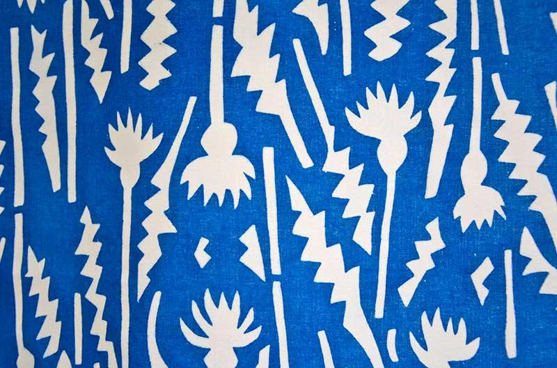 Mönster med stiliserade tistlar i vitt mot klarblå botten.