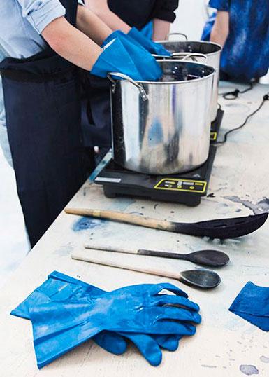 En person med blå gummihandskar färgar in tyg i indigoblått färgbad. På bordet en kastrull med färgbadet och olika redskap i trä.