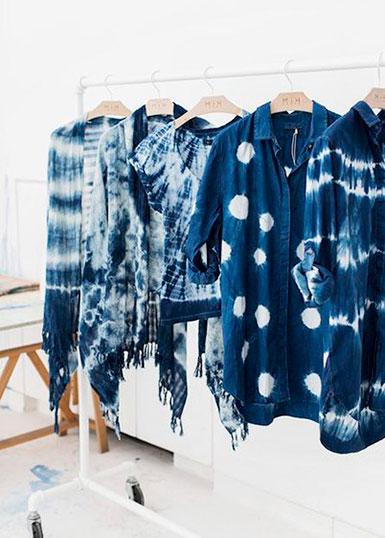Fem indigoblå skjortor/toppar med olika shiborimönster i vitt. Plaggen hänger på galgar på en klädstång.