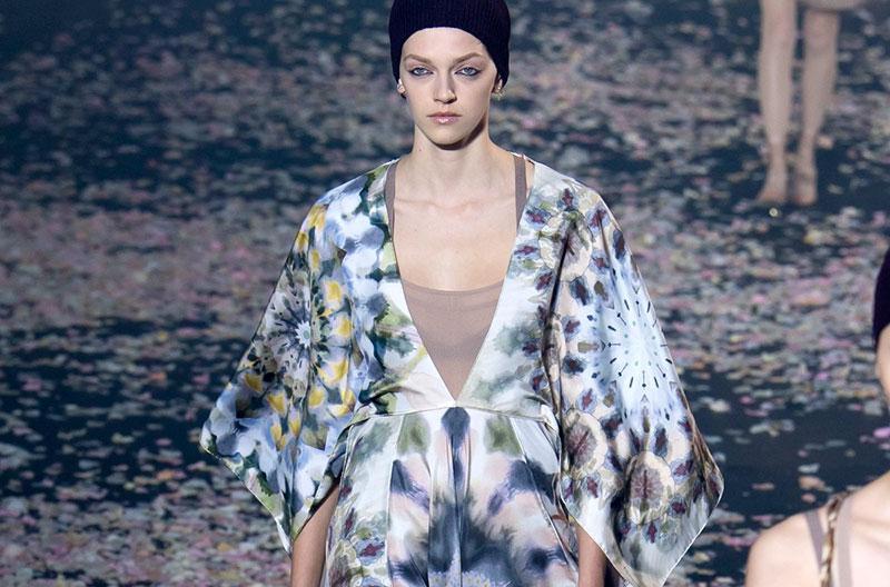 En modell visar ett Christian Dior-plagg på catwalken. Plagget är en klänning med stora shiborimönster i pastellfärger.