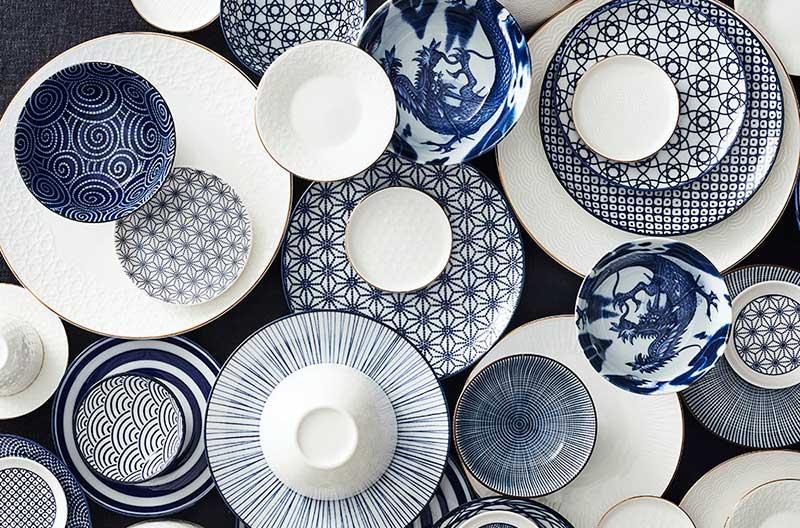 Tallrikar, assietter och skålar med olika mönster i vitt och indigoblått. Det är både organiska mönster och strikta, geometriska mönster.