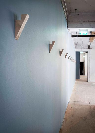 Blå vägg med ett antal krokar som består av kilformade bitar av björk.