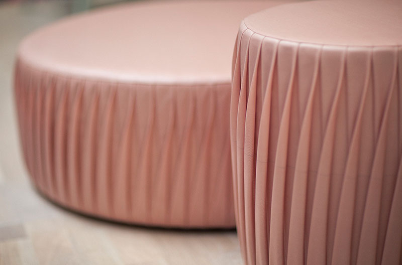 En hög och en låg sittpuff i ett rosa veckat plastmaterial.