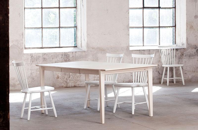 Fyra vita pinnstolar i klassisk design vid ett bord i björk och en ljus lokal med betongväggar.