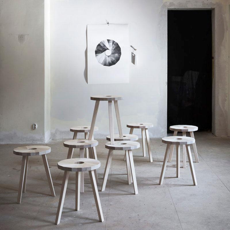 Nio exemplar av pallen Lilla Snåland i industrilokal. På väggen en poster med ett grafiskt tryck av pallens karaktäristiska sits.