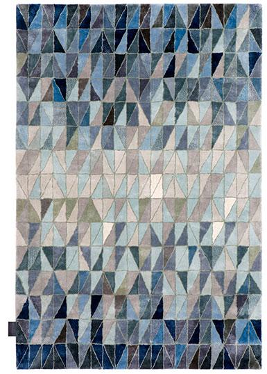 Matta med ett mönster som består av kilformade bitar i olika blå och grå nyanser.